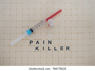 Tan tiles with black capital letters spelling pain killer set in a background of small tan tiles. A labeled syringe with needle and an empty glass fentanyl vial are pictured. Photographed from above.