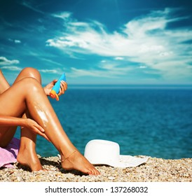 Tan Woman Applying Sunscreen on Legs