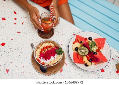 Tan woman chilling and enjoying breakfast during holidays in Bali. Stylish tropical outfit, summer mood.   Vegetarian food. Smoothie bowl, fruit plate and lemonade. Top view.