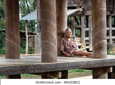 Tana Toraja, Indonesia - Dec 09, 2015: Unidentified Indonesian elderly man sits under the floor of tongkonan traditional house in Lempo village. South Sulawesi