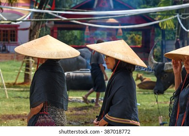 Tana Toraja, Indonesia - Dec 10, 2015:  Unidentified group of women in black and conical straw hats at funeral ceremony.