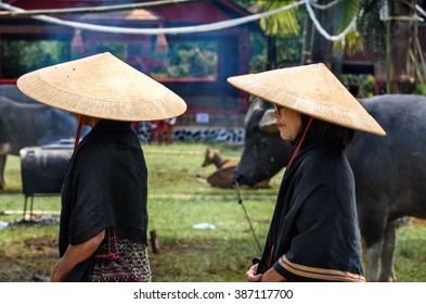 Tana Toraja, Indonesia - Dec 10, 2015:  Unidentified group of women in black and conical straw hats at funeral ceremony. In Toraja the funeral ritual is the most elaborate and expensive even
