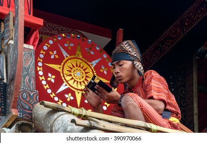 Tana Toraja, Indonesia - Dec 10, 2015:  Unidentified boy in traditional clothes near the coffin at funeral ceremony. In Toraja the funeral ritual is the most elaborate and expensive even