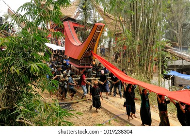 Tana Toraja, Indonesia - october 2009 :  the evocative procession during a typical Toraja funeral. The men carry the elaborate and heavy coffin, the women in front hold a long red cloth