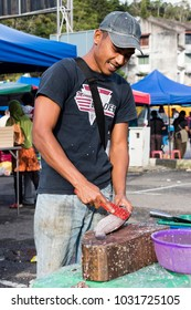 Tanah Rata, Malaysia, December 17 2017: Seller scrapes the scales of a fish with a knife