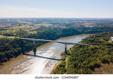 Tancredo Neves Bridge, Fraternity Bridge (Ponte da Fraternidade, Puente de la Fraternidad) border crossing over the Iguassu River and the town of Puerto Iguazú. Brazil — Argentina. Aerial drone photo.