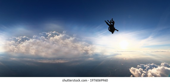 Tandam skydiving banner. Background of the sun and clouds in free fall.Man conquers the sky and flies upside down.Aerodynamics. 4000 meters above the ground. Extreme tourism.National airborne day