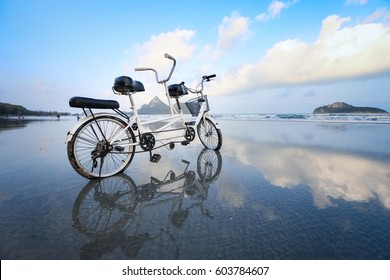 Tandem Bicycle on the beach with its reflection on the beach, grain texture style apply
