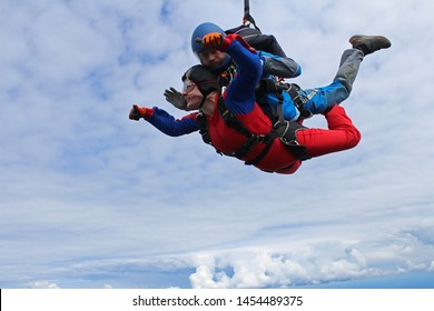Tandem jump. Woman and man are falling in the sky together.