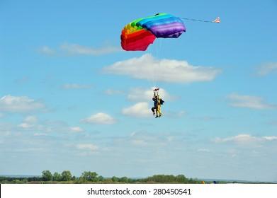 Tandem multicolored parachute land against cloudy blue sky