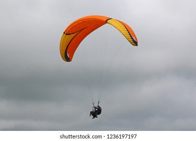 Tandem paraglider in a cloudy sky
