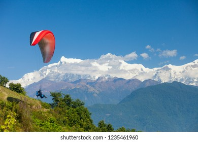 A tandem paraglider takes off over Pokhara, Nepal