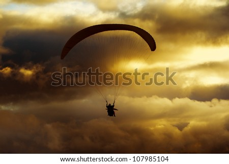 Tandem Paragliders At Dusk Overworked In Postproduction To Add More Drama And Color Intensity