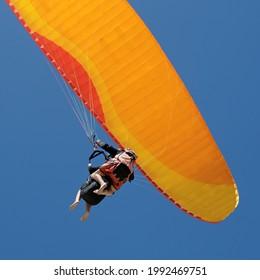 Parapente en tandem baptême en gros plan sur la Dune du Pyla avec fond bleu ciel
