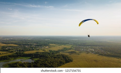 Tandem paragliding. Time before sunset. Beautiful flight over the plain. Green fields underfoot. Extreme and adrenaline. The blue-yellow wing flies against the background of the earth.