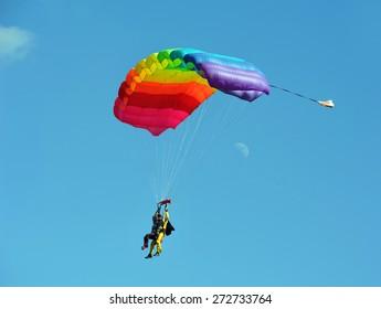 Tandem rainbow-colored parachute against clear blue sky