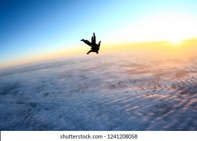 Tandem skydiving, flying above the Earth during sunset.