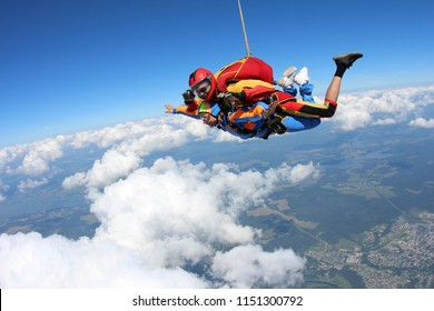 Tandem skydiving. Girl-passenger is flying in the amazing sky.