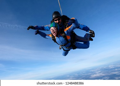 Tandem skydiving. Happy girl is in the sky.
