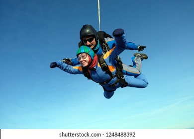 Tandem skydiving. Happy girl is in the sky.