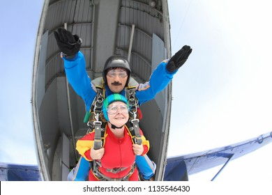 Tandem skydiving. Man and woman are jumping out of a plane.