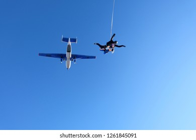 Tandem skydiving. Skydivers have just jumped out into amazing blue sky.