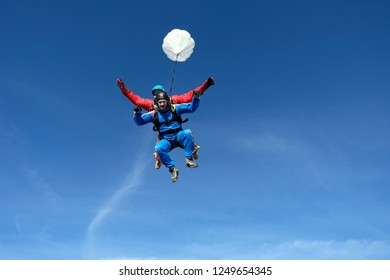 Tandem skydiving. Two happy men are falling in the blue sky.