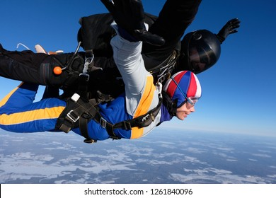 Tandem skydiving in winter period. A girl-passenger is happy when she flies above snowy land.