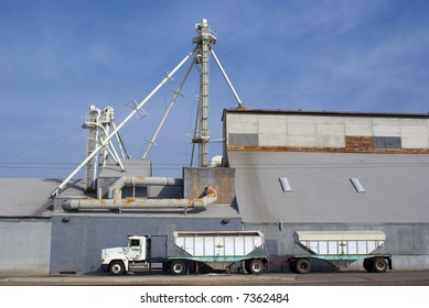 A tandem trailer truck rig awaits loading at a fertilizer plant