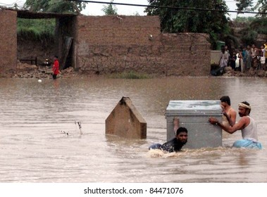 TANDO ADAM, PAKISTAN -SEPT 10: Rain affected people with their houses pass through a flooded area as they are moving towards safe place after their houses were inundated with rainwater September 10,2011.