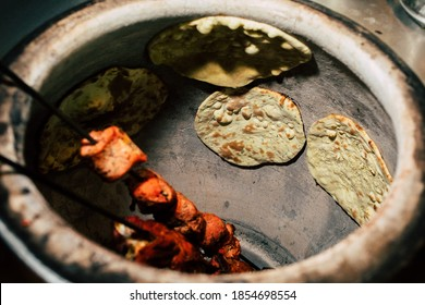 Tandoor oven with tikka masala chicken and naan. Original and traditional Indian cuisine