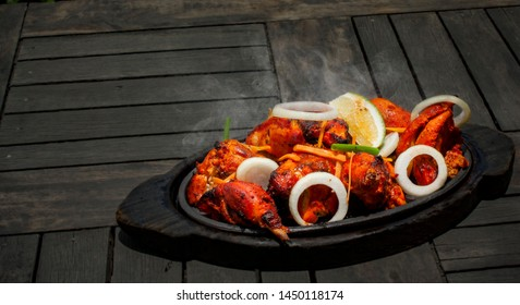 Tandoori chicken is a chicken dish prepared by roasting chicken marinated in yogurt and spices in a tandoor, a cylindrical clay oven. The dish originated from the Indian subcontinent and is popular i