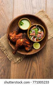 Tandoori chicken - prepared by roasting chicken marinated in yoghurt and spices in a tandoor. Leg pieces served in a plate with salad and chutney over colourful or wooden background. Selective focus
