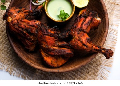 Tandoori chicken - prepared by roasting chicken marinated in yoghurt and spices in a tandoor. Leg pieces served in a plate with salad & chutney over colourful or wooden background. Selective focus