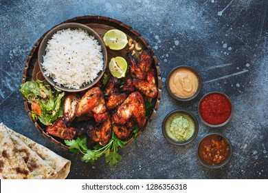 Tandoori chicken wings served with pilau rice,  soft garlic cheese naan with different chutney dipping sauces. Top view, blank space, rustic background