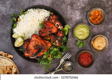 Tandoori chicken wings with spicy pilau rice, lime and traditional assortment of sauces on rustic table, top view