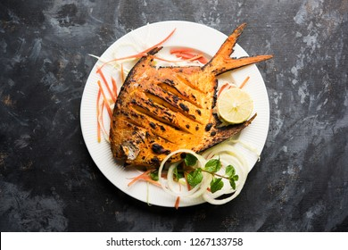 Tandoori Pomfret fish cooked in a clay oven and garnished with lemon , mint, cabbage and carrot salad. Selective focus