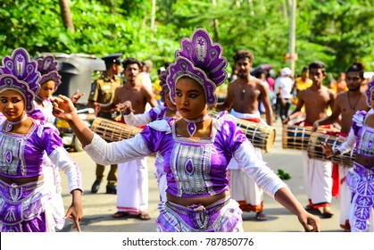 Tangalle, Sri Lanka - August 12 2017: Traditional dancers in colorful dress performing on the street during Buddhist procession called Perahera, one of the most important event in Buddhist tradition.