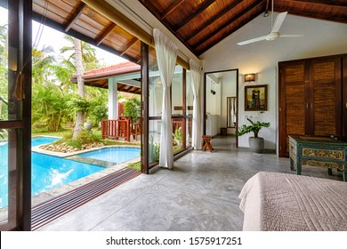 Tangalle, Sri Lanka - Oct 31, 2017: Villa with pool and garden in tropical hotel. Panoramic view of ethnic style interior. Luxury backyard to relax. Vacation home or resort house with beautiful yard.