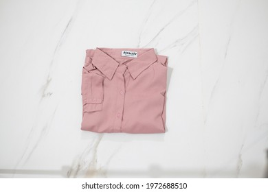 TANGERANG SELATAN, INDONESIA - NOV 25th, 2019 - Pink women shirt by Atractiv with white marble background