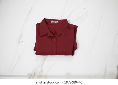 TANGERANG SELATAN, INDONESIA - NOV 25th, 2019 - Red color women shirt by Atractiv with white marble background