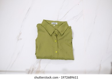 TANGERANG SELATAN, INDONESIA - NOV 25th, 2019 - Young Green color women shirt by Atractiv with white marble background