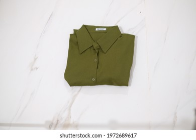 TANGERANG SELATAN, INDONESIA - NOV 25th, 2019 - Green color women shirt by Atractiv with white marble background