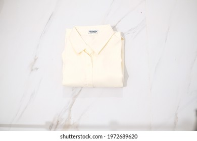 TANGERANG SELATAN, INDONESIA - NOV 25th, 2019 - Cream color women shirt by Atractiv with white marble background
