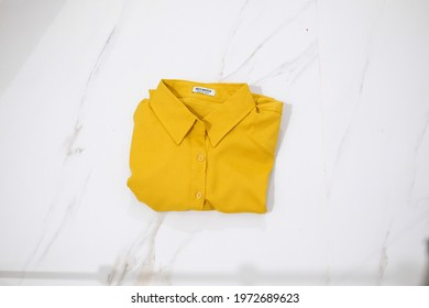 TANGERANG SELATAN, INDONESIA - NOV 25th, 2019 - Yellow color women shirt by Atractiv with white marble background