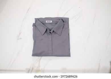 TANGERANG SELATAN, INDONESIA - NOV 25th, 2019 - Grey color women shirt by Atractiv with white marble background