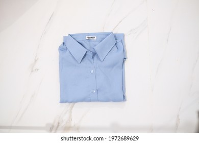 TANGERANG SELATAN, INDONESIA - NOV 25th, 2019 - Blue color women shirt by Atractiv with white marble background