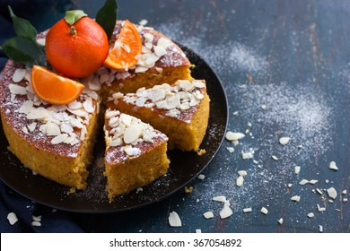tangerine and almond cake on dark blue background, selective focus