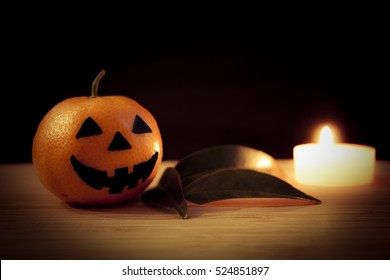 Tangerine - Halloween pumpkin with candle and leaves on a dark background. Still life picture taken in studio.