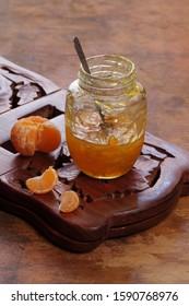 Tangerine jam on white wooden background